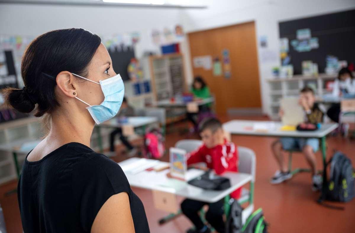 Eine Lehrerin steht mit Maske vor ihrer Grundschulklasse. Foto: dpa/Sebastian Gollnow
