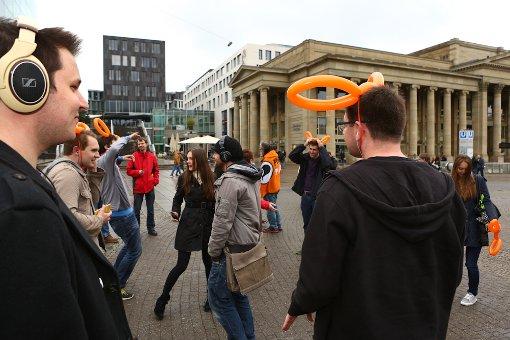 Kopfhörer auf, Musik an und losgetanzt: Auf dem Schlossplatz haben sich Gegner des Tanzverbots auf Initiative der Piraten Partei zum stillen Abzappeln getroffen. Foto: Benjamin Beytekin