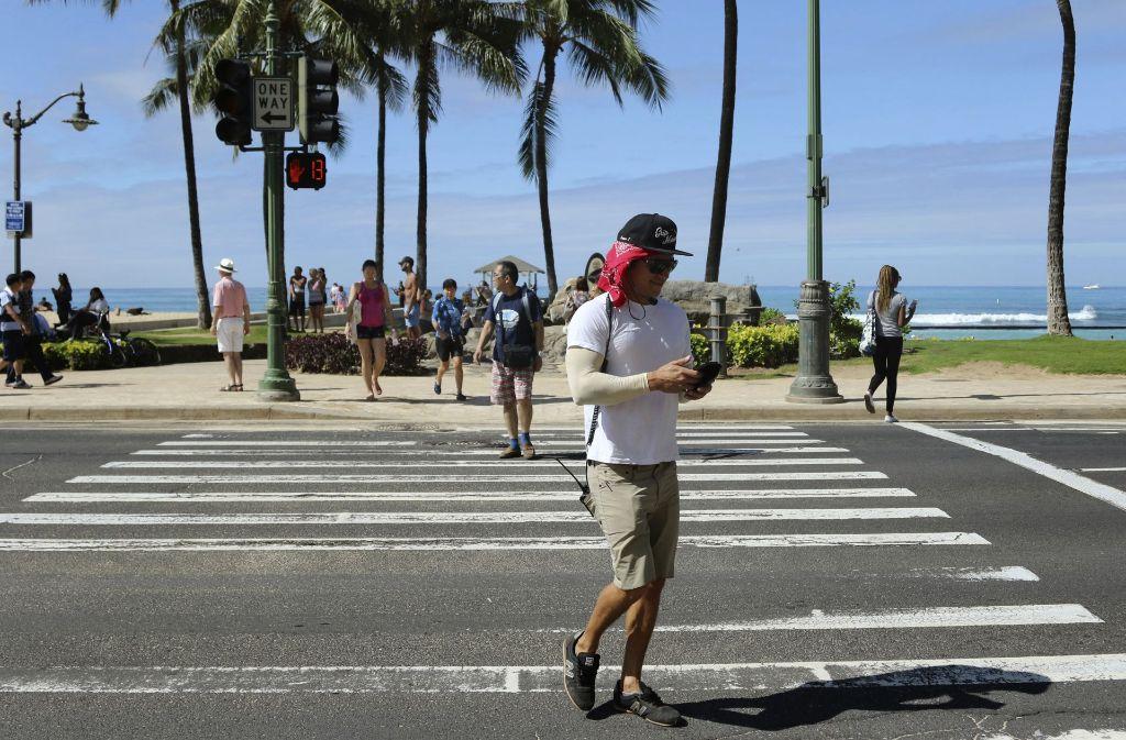 Ein Mann überquert in Honolulu einen Zebrastreifen und schaut dabei auf sein Smartphone. Wir er erwischt, kann das bis zu 35 Dollar kosten. Foto: AP