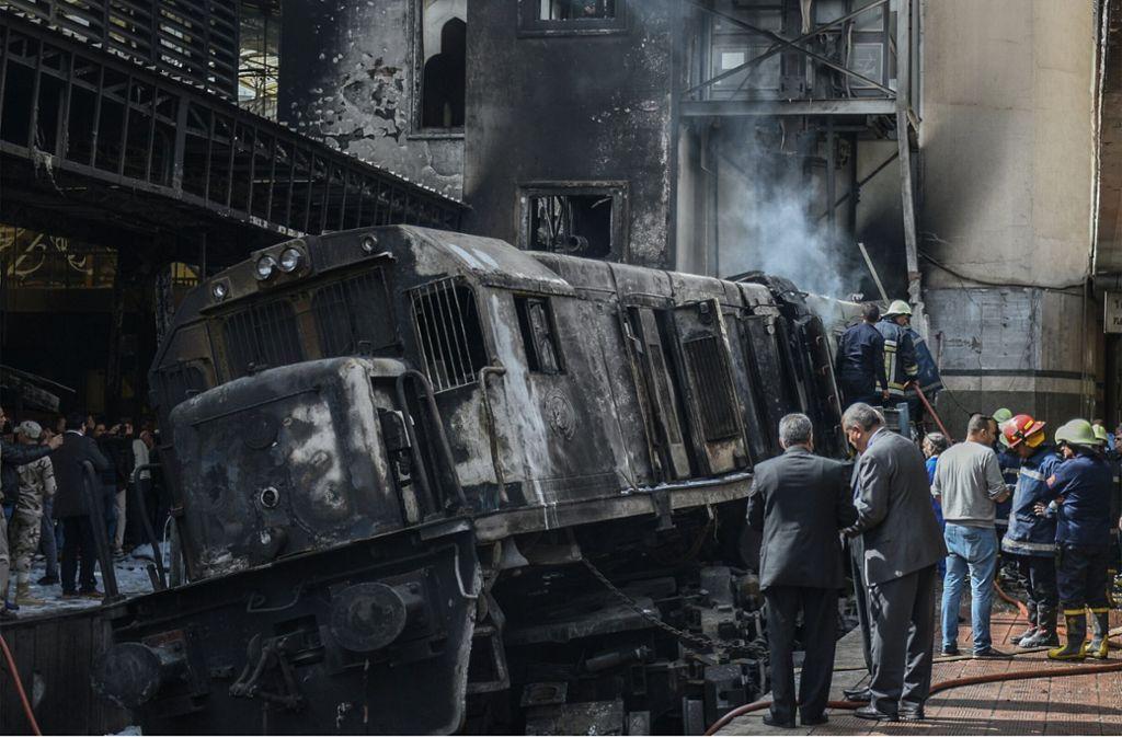 Feuerwehrmänner und Rettungskräfte stehen neben dem ausgebrannten Zug im Bahnhof der ägyptischen Hauptstadt. Foto: dpa