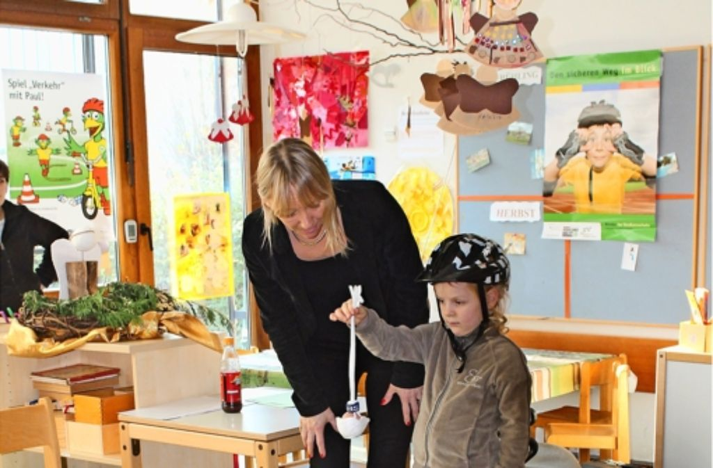 Birgit Weber von der Verkehrswacht zeigt anhand eines rohen Eis, wie wichtig es ist, einen Helm zu tragen, um sich vor Kopfverletzungen zu schützen. Foto: Sabine Schwieder
