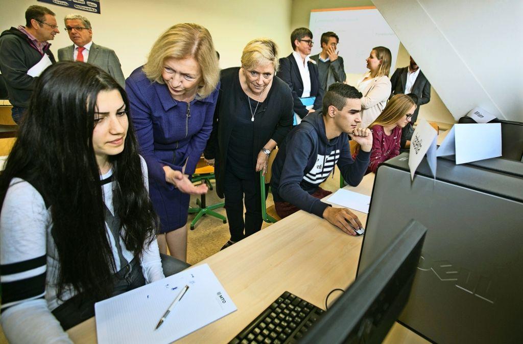 Die Bundesministerin Johanna Wanka  (links) und die Landesministerin Susanne Eisenmann schauen den Schülern bei der Potenzialanalyse über die Schultern. Foto: Horst Rudel