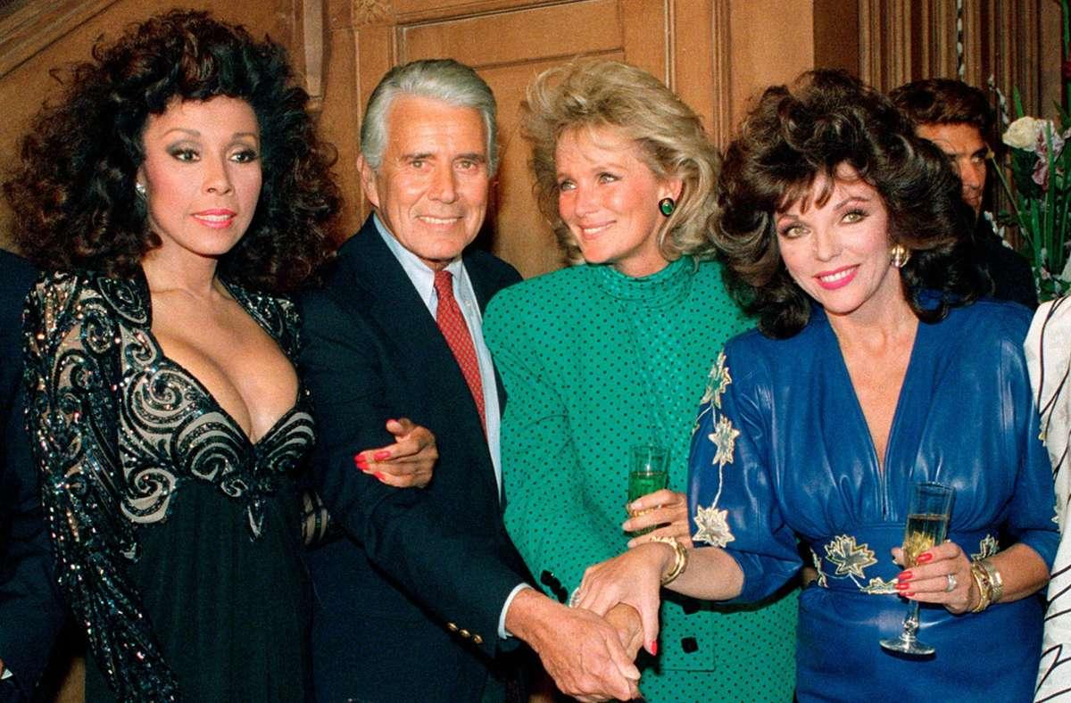 """Die Schauspieler Diahann Carroll,  John Forsythe, Linda Evans und Joan Collins (v. li.) 1986 beim Feiern anlässlich der 150. Folge von """"Denver-Clan"""". Foto: dpa/Reed Saxon"""