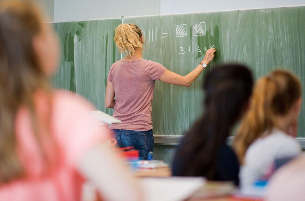 Eine Lehrerin an der Tafel: Wie weit dürfen Pädagogen in der Schule mit persönlichen Meinungsäußerungen gehen? Foto: dpa/Julian Stratenschulte