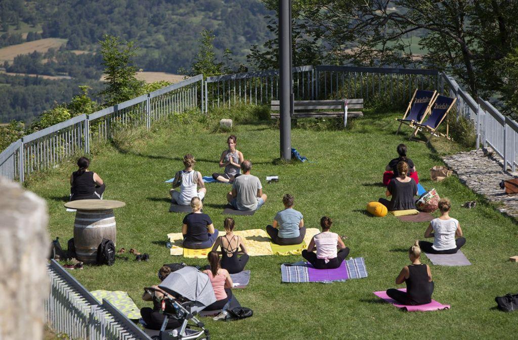 Konzentration bitte: Beim Yoga auf dem Hohenneuffen haben die Teilnehmer einen tollen Ausblick – und dank der vielen Besucher auch Zuschauer. Foto: Michael Steinert