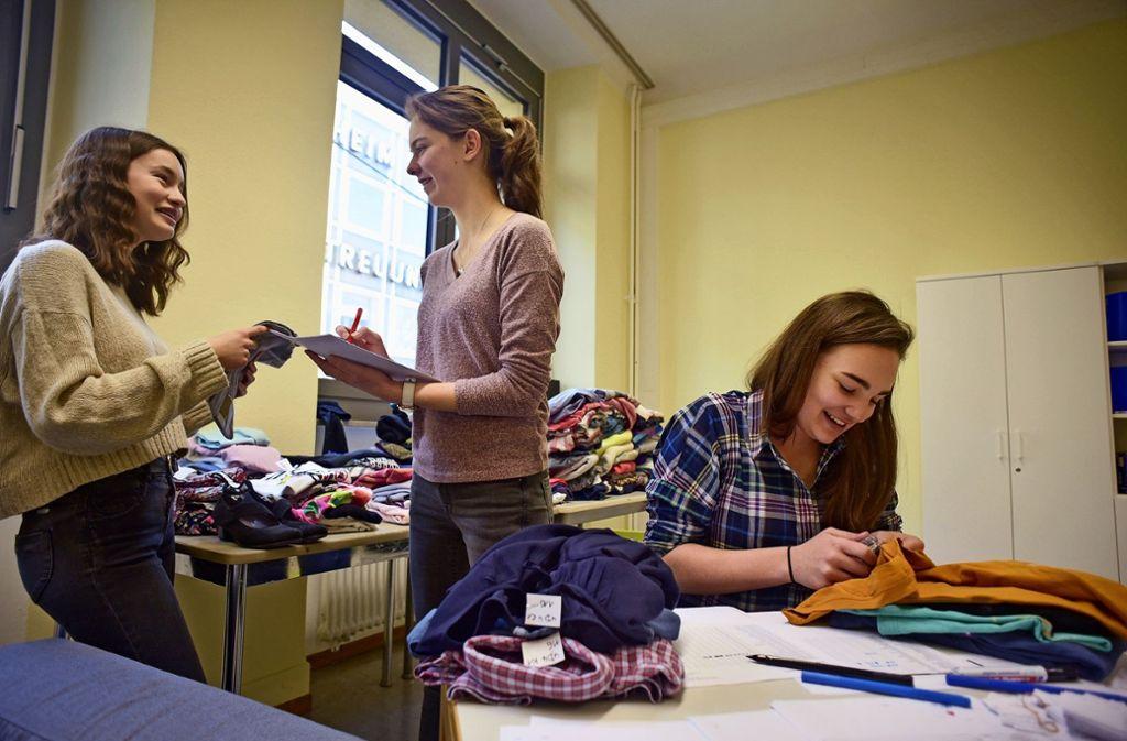 Laura Stern, Friederike Schloe und Tabea Kury sortieren Kleidung. Foto: Lichtgut/Max Kovalenko