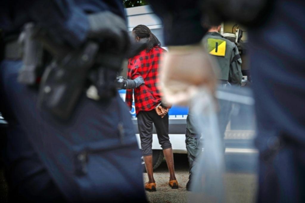 Polizisten führen einen der Verdächtigen  in Handschellen ab. Foto: Gottfried Stoppel