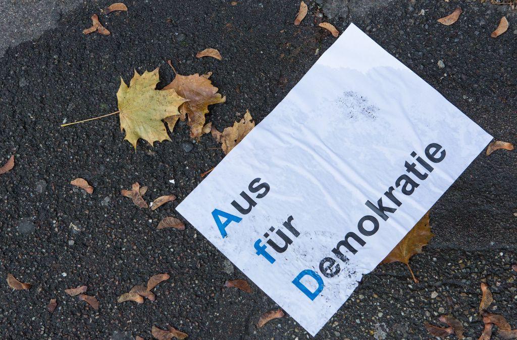 """Demonstranten haben ein Plakat in Kelhl auf den Boden geworfen: """"Aus für Demokratie"""" steht darauf. Die AfD hat bei ihrem Parteitag die Öffentlichkeit ausgeschlossen. Foto: dpa"""