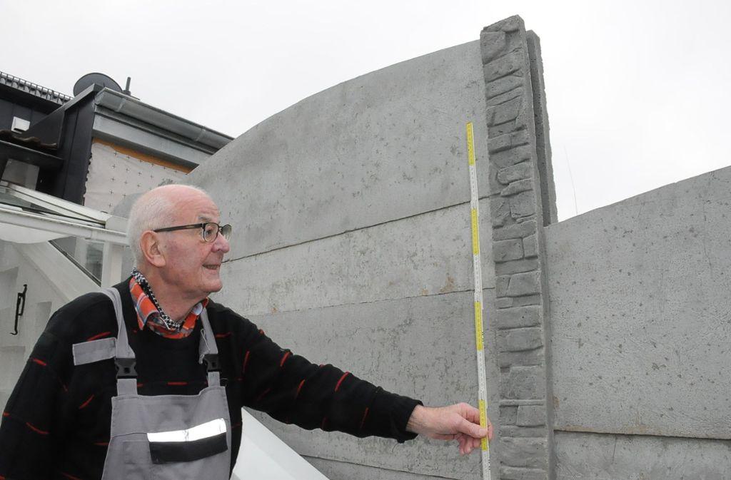 Günther Mayer legt den Zollstock an: Mehr als zwei Meter misst die Mauer  des Nachbarn an der höchsten Stelle. Das darf nicht sein, findet nicht nur  der Senior. Foto: Georg Linsenmann