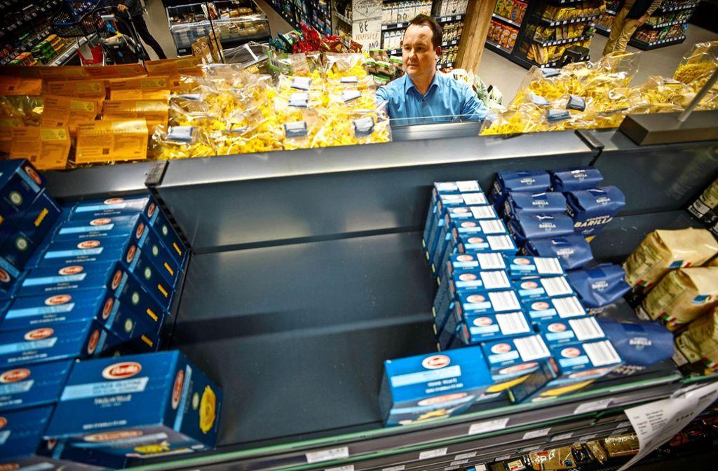Noch sind die Regale gut  gefüllt: Inhaber Björn Hansen wirft einen prüfenden Blick auf die Nudelprodukte des Edeka-Markts in Fellbach. Foto: Gottfried Stoppel
