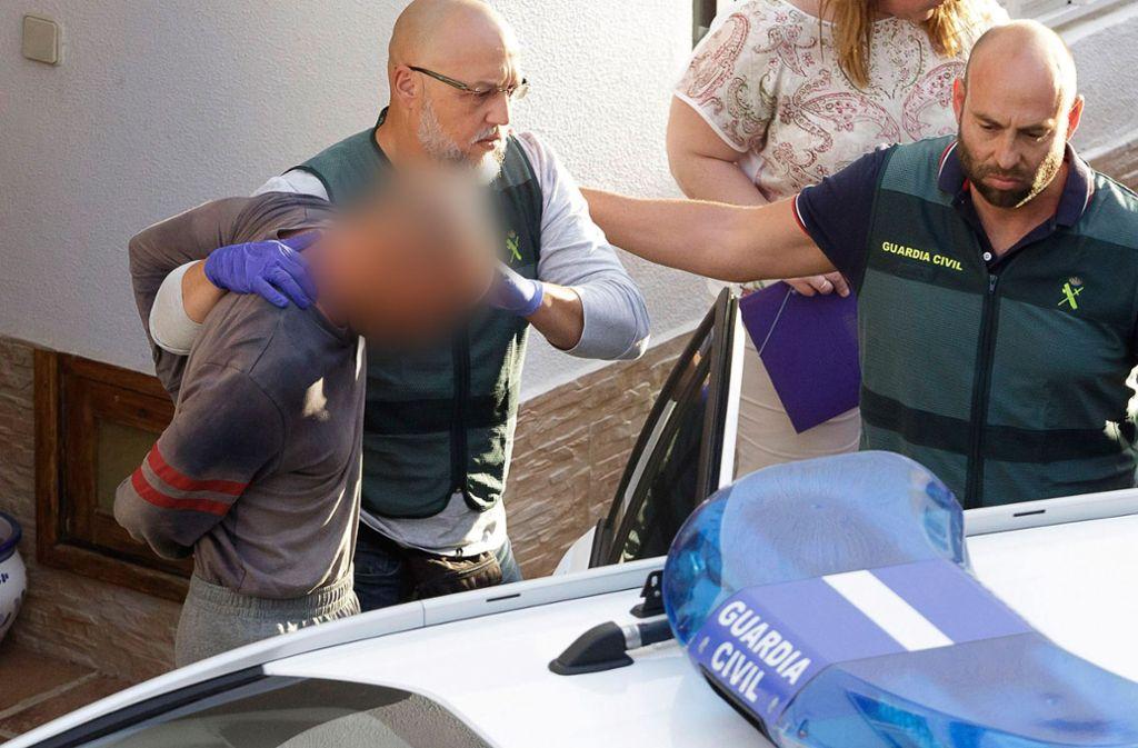 Der Familienvater wird nach einer Hausdurchsuchung abgeführt. Foto: AP