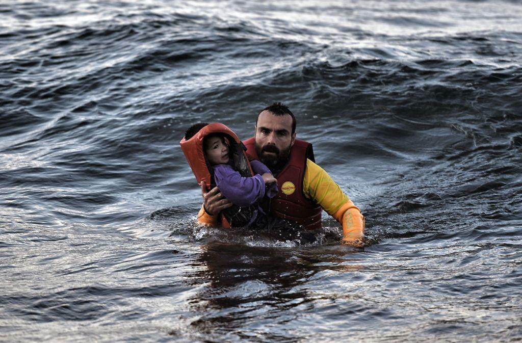 Ein spanischer Helfer rettet 2015 ein Kind, das auf einem sinkenden Schiff unterwegs war, aus dem Mittelmeer. Foto: AFP
