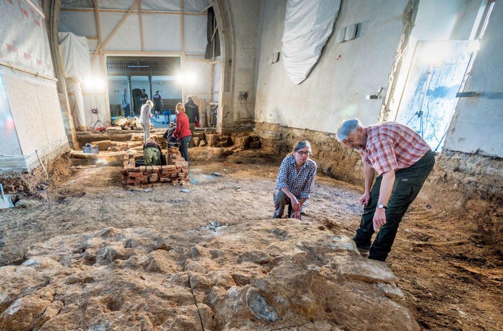 Der Kreisarchäologe Reinhard Rademacher begutachtet mit einer Kollegin einen Unterbau aus Stein, den sie in der Erde unter dem früheren Boden der Cäcilienkirche in Uhingen entdeckt haben. Foto: Giacinto Carlucci