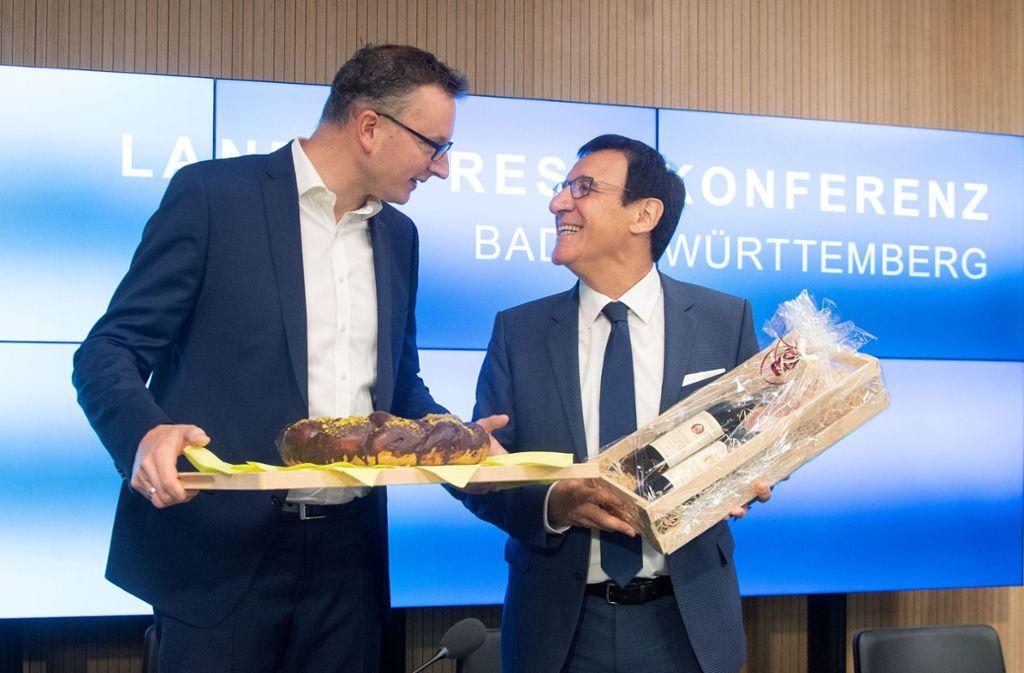 Grünen-Fraktionschef Schwarz (li.) bringt seinem CDU-Kollegen Hefezopf, dieser revanchiert sich mit Wein. Foto: dpa