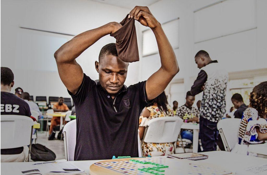 Wellington Jighere bei einer Partie Scrabble in Lagos. Aus dem Stoffbeutel über seinen Augen zieht er neue Buchstabensteine Foto: Putsch