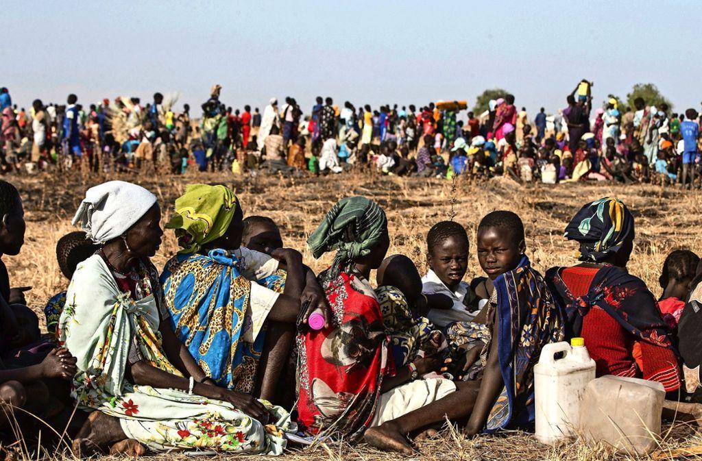 Kinder und Frauen  warten im Südsudan auf Hilfslieferungen. Hilfe in dem armen Land ist dringend notwendig. Foto: dpa/Modola