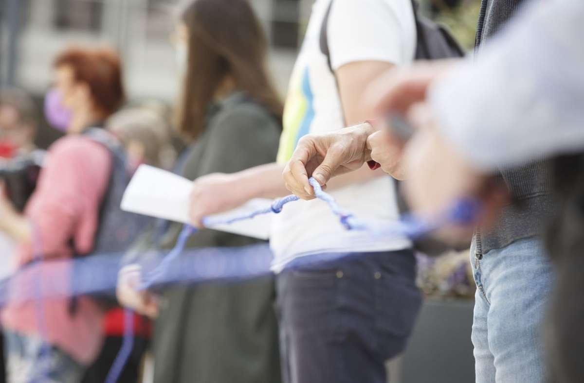 Teilnehmer der Kundgebung in Stuttgart halten eine Leine als Symbol für eine Rettungskette. Foto: Lichtgut/Julian Rettig