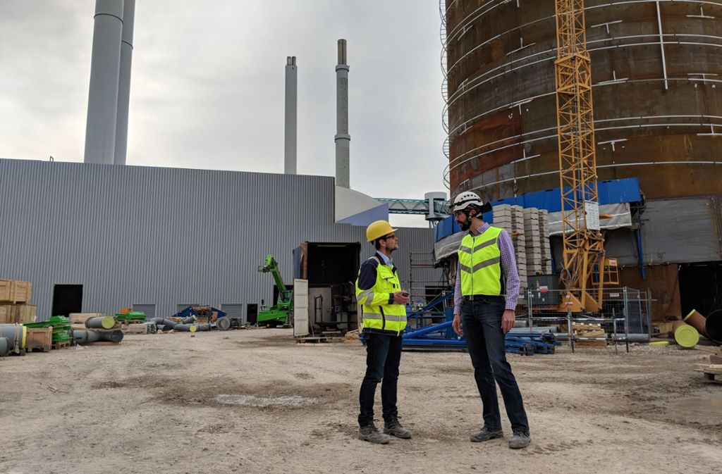 Der Projektleiter Jens Rathert (links) und der Oberbauleiter Christoph Greiner diskutieren vor dem 40 Meter hohen Wärmespeicher technische Details. Foto: Jürgen Brand