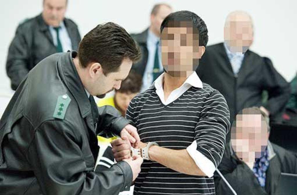 Ein Justizbeamte befreit einen Angeklagten von seinen Handschellen. Im Prozess gab die Richterin vorläufige Urteile bekannt. Foto: dpa