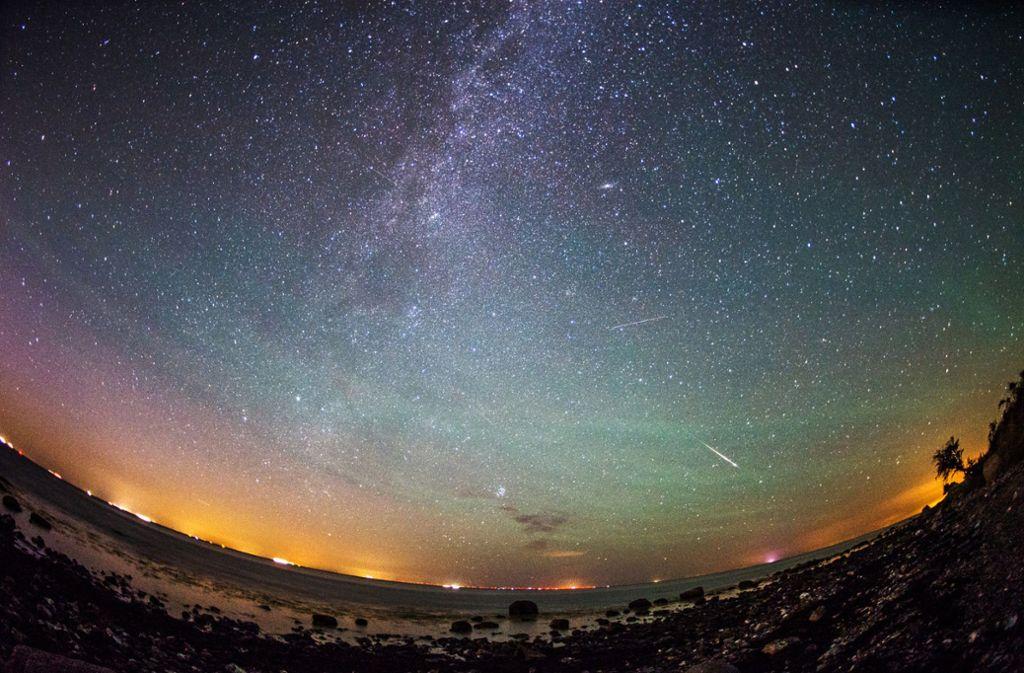 Mehrere Sternschnuppen sind am 13. August  auf Fehmarn (Schleswig-Holstein) am klaren Nachthimmel rechts neben der Milchstraße zu sehen.   Foto: Daniel Reinhardt/dpa