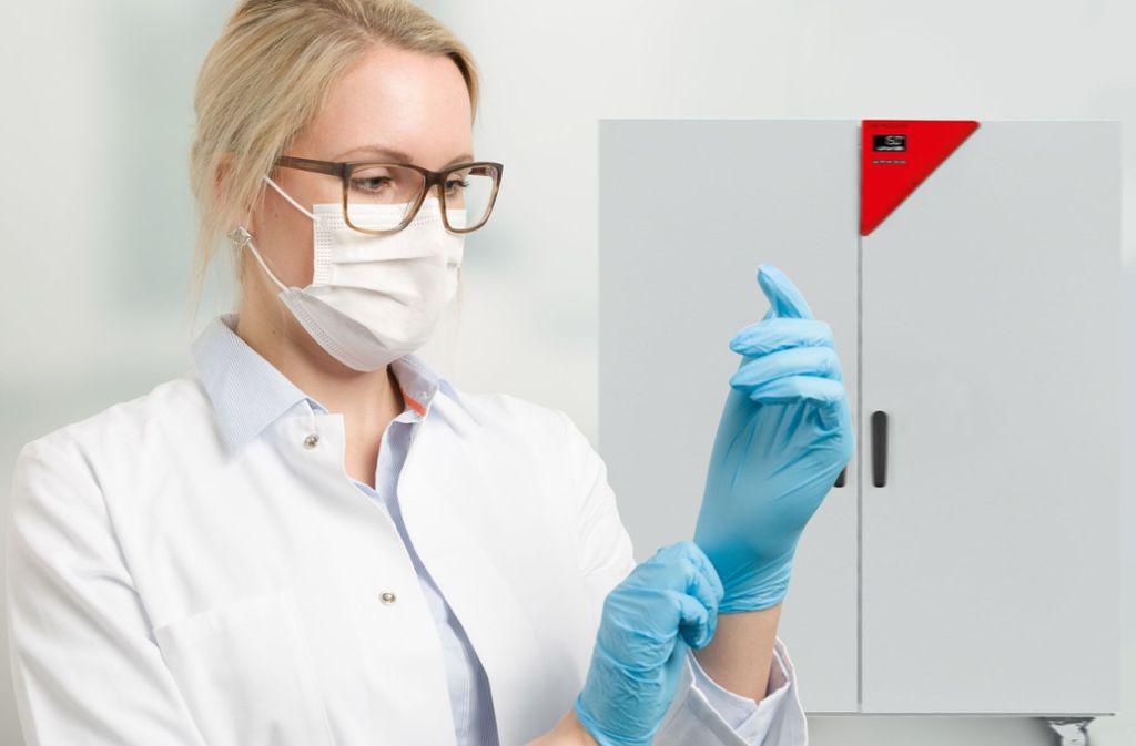 Eine Beschäftigte  steht mit ihrem Schutz für Mund und Nase vor einem Schrank von Binder zum Trocknen von Masken. Foto: