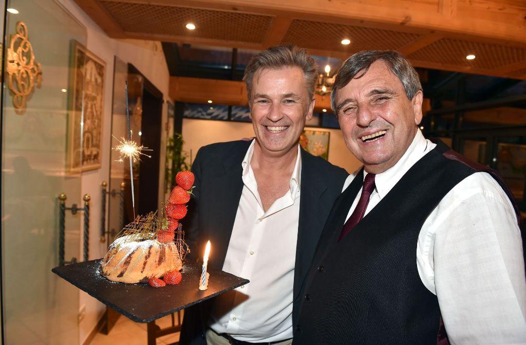 Vom Gastgeber und Restaurantbesitzer Peter Pongratz (rechts) gibt es einen Geburtstagskuchen für Schauspieler Timothy Peach. Foto: Getty Images Europe