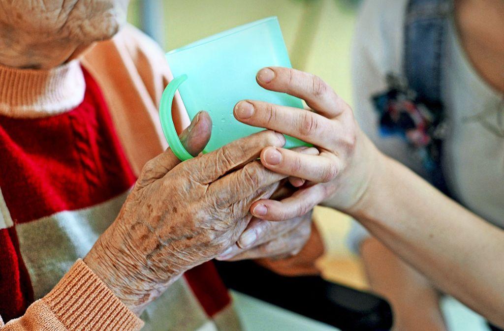 Eine Pflegekraft hilft einer alten Frau beim Trinken aus einem Becher. Foto: dpa