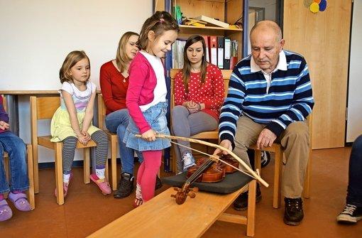 Ahmed Baydur (l.) lässt die Kinder ausprobieren, wie eine Geige klingt. Foto: Leonie Schüler