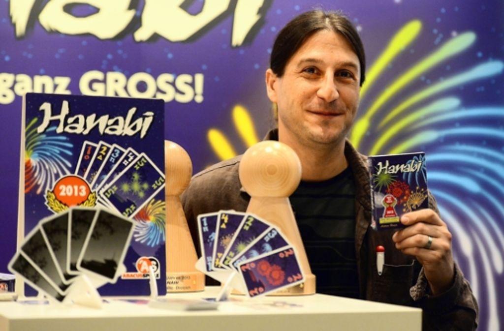 """Der französische Autor Antoine Bauza (links) und sein Spiel """"Hanabi"""". Foto: dpa"""