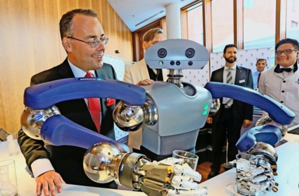 """Roboter Hollie (im Bild mit Bundesratsminister Peter Friedrich) mixte für die Gäste  vollautomatisch """"Cyber-Drinks"""". Foto: dpa"""