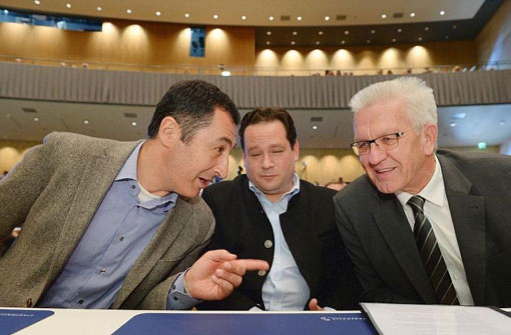 Cem Özdemir (links) unterhält sich am 8. November in der Stadthalle in Tuttlingen  beim Landesparteitag von Bündnis 90/Die Grünen mit dem baden-württembergischen Ministerpräsidenten Winfried Kretschmann (rechts) und Alexander Bonde. Foto: dpa