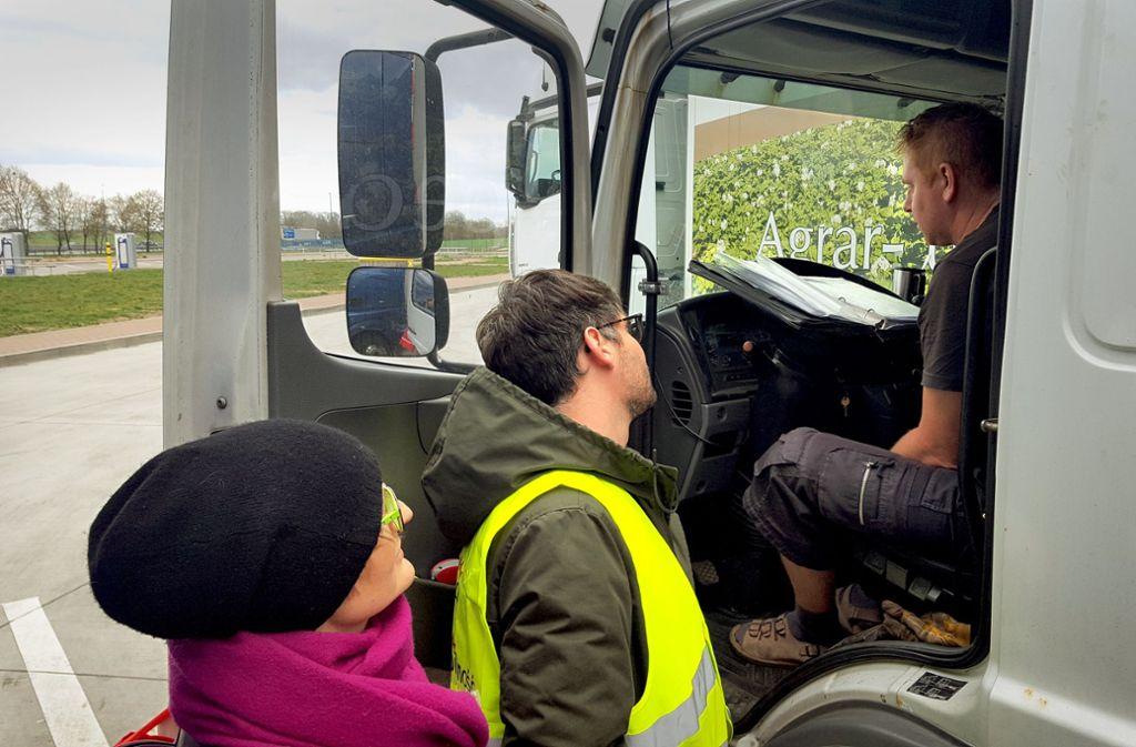 Michael Wahl (Mitte) spricht einen polnischen Fahrer auf seine Arbeitsbedingungen an. Die Parlamentarierin Franziska Brantner lauscht interessiert. Foto: Schiermeyer