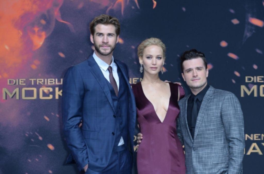 Die Schauspieler Josh Hutchinson, Jennifer Lawrence und Liam Hemsworth (von rechts) bei der Weltpremiere des Abschlussfilms «Die Tribute von Panem - Mockingjay Teil 2» auf dem Roten Teppich vor dem Cinestar-Kino in Berlin. Foto: dpa