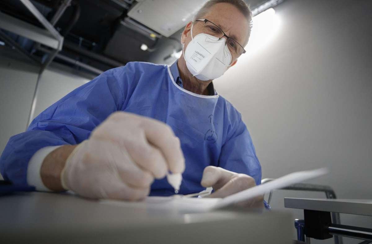 Peter Hartung steckt das  Stäbchen, mit dem er einen Nasenabstrich gemacht hat, in die Testvorrichtung Foto: Gottfried Stoppel