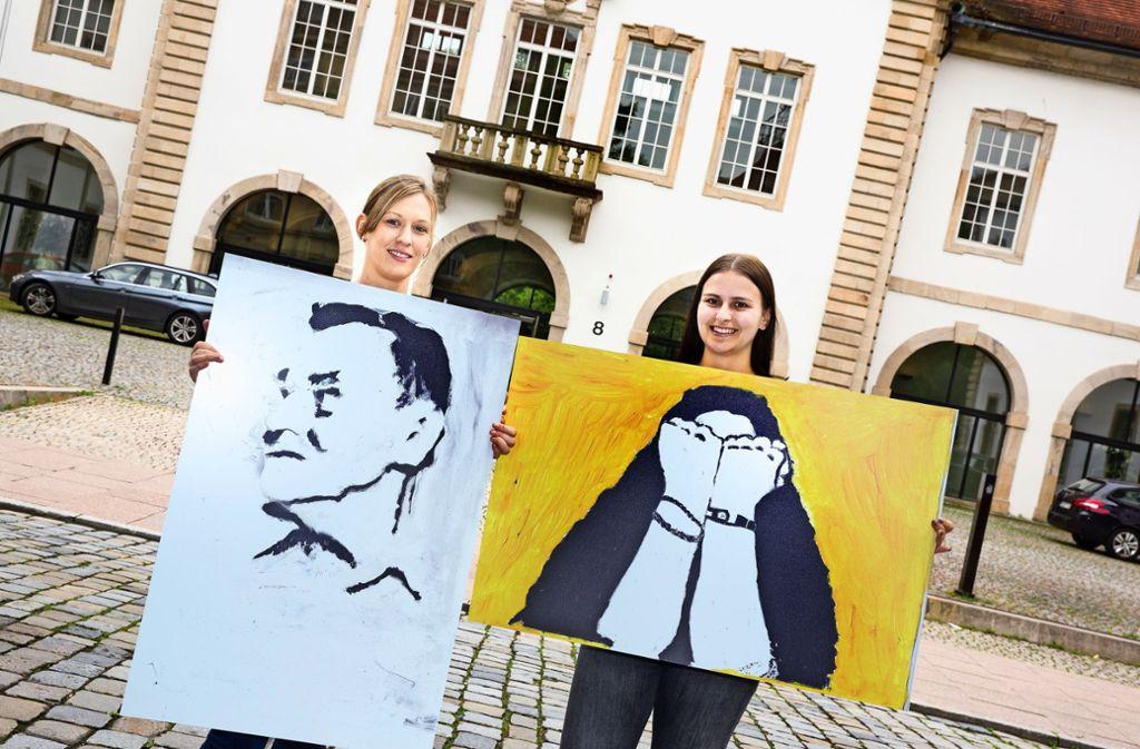 Sabine Kubinski (links) und Celine-Marie Wehrstein von Prävent Sozial präsentieren vorab zwei Porträts aus der Ausstellung vor dem Esslinger Amtsgericht. Foto: