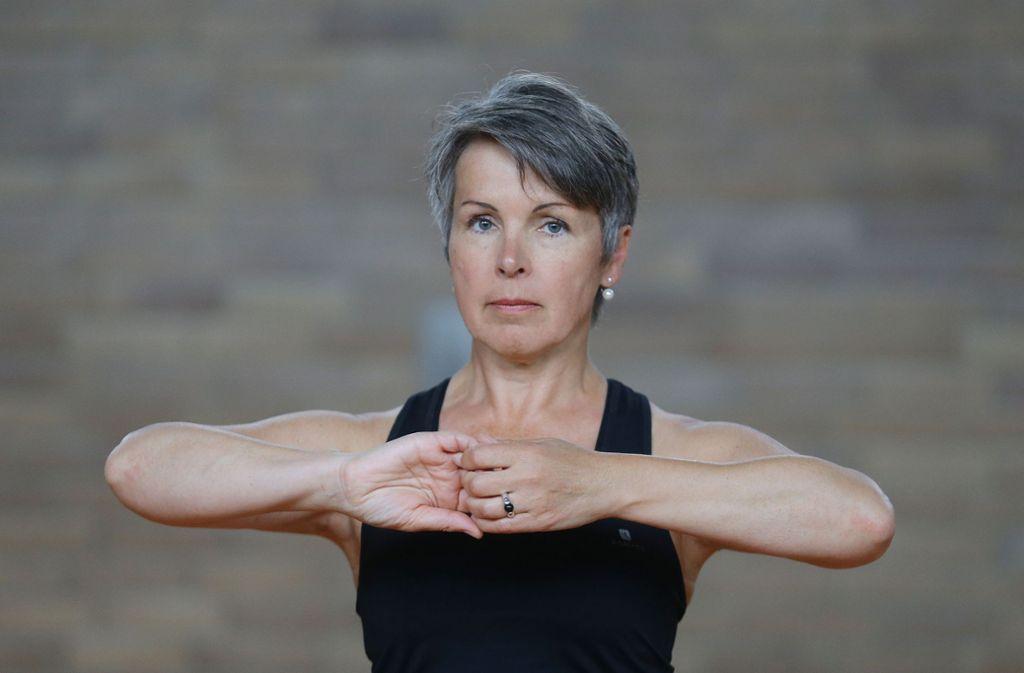 So geht's los: die Finger vor der Brust verhaken und die Ellbogen auf Höhe der Hände sanft nach außen ziehen. Foto: Baumann