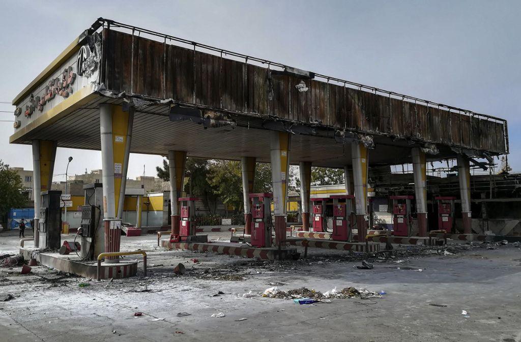 Eine bei Protesten gegen die Verteuerung und Rationierung von Benzin abgebrannte Tankstelle. Foto: dpa/Anmar Khalil