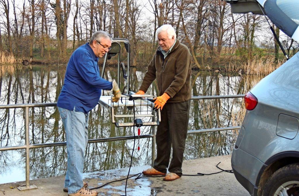 Wolfgang Lutz (links) und Jürgen Dietrich hieven einen von drei Gepäcktrolleys aus dem Langwieser See. Die stammen vom nahen Flughafen und sind mutmaßlich von Jugendlichen hier versenkt worden, die sich einen vermeintlichen Spaß machen wollten. Foto: privat