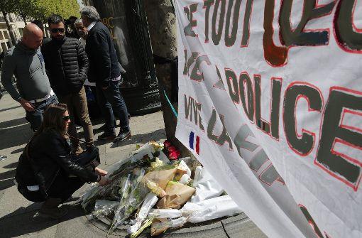 Nach dem Anschlag in Paris zeigen Passanten ihre Solidarität mit den Polizisten. Foto: AP