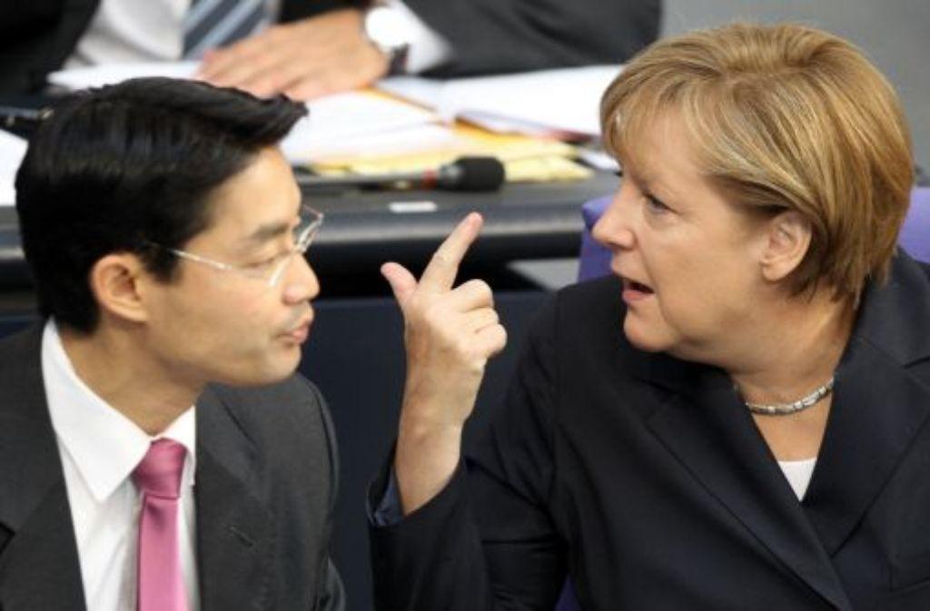 Kanzlerin Angela Merkel (CDU, hier mit Philipp Rösler) sieht trotz des Wahldesasters der FDP in Berlin und des Euro-Streits keine Belastung für die Arbeit der schwarz-gelben Koalition. Foto: dpa