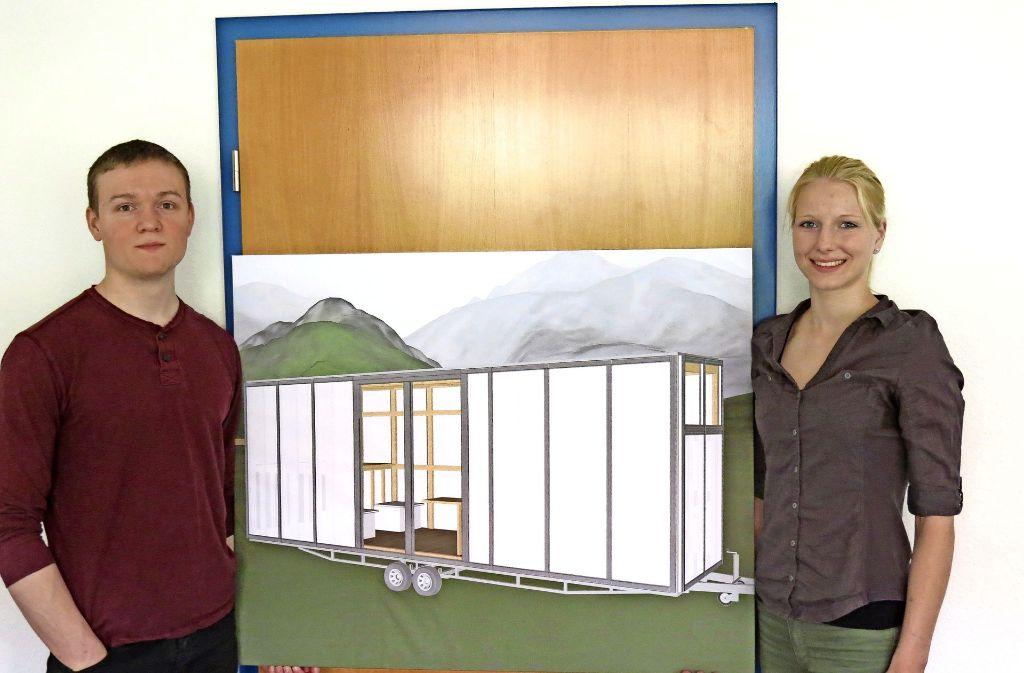 Brendan Thome und Sina Martensen zeigen auf einem Plakat, wie die Tech Tiny Houses aussehen werden. Foto: Julia Bosch