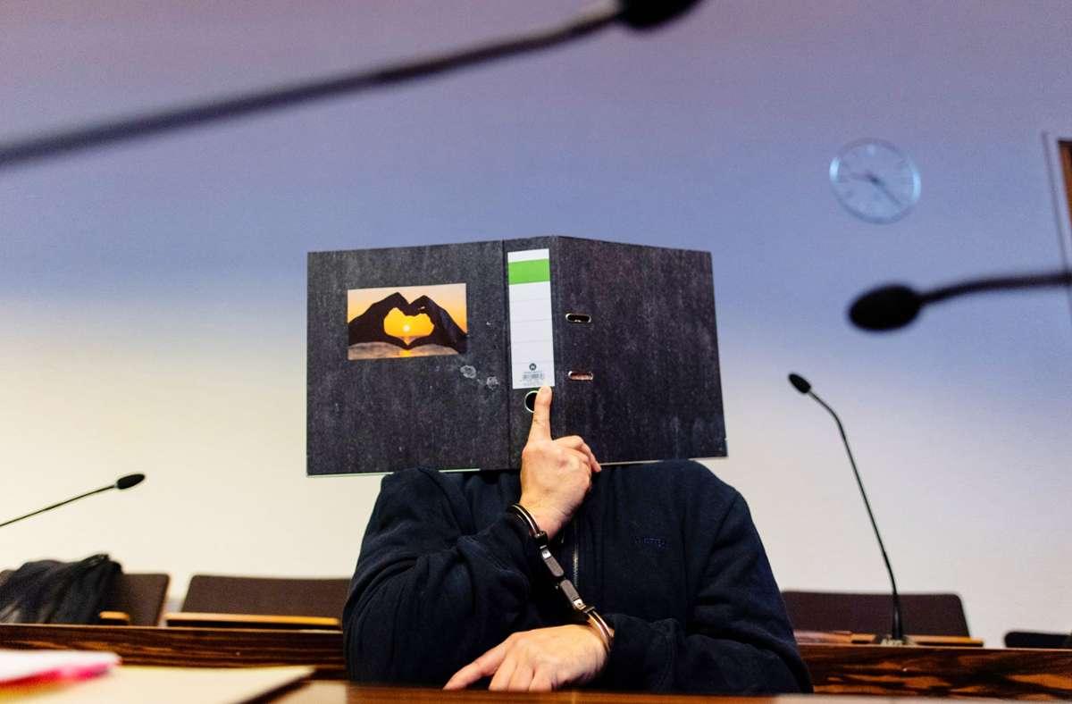 Zu Beginn der Hauptverhandlung klebt auf dem Aktenordner, mit dem Bernhard H. sein Gesicht vor den Kameras schützt, ein Bild, auf dem zwei Hände ein Herz bilden – eine Botschaft an die Prozessbeobachterin und Zeugin Maria Henselmann. Foto: dpa/Patrick Seeger