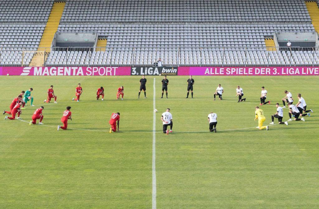 Die Bayern- und Münster-Spieler knien vor dem Spiel am Mittelkreis. Foto: imago images/Passion2Press/Markus Fischer