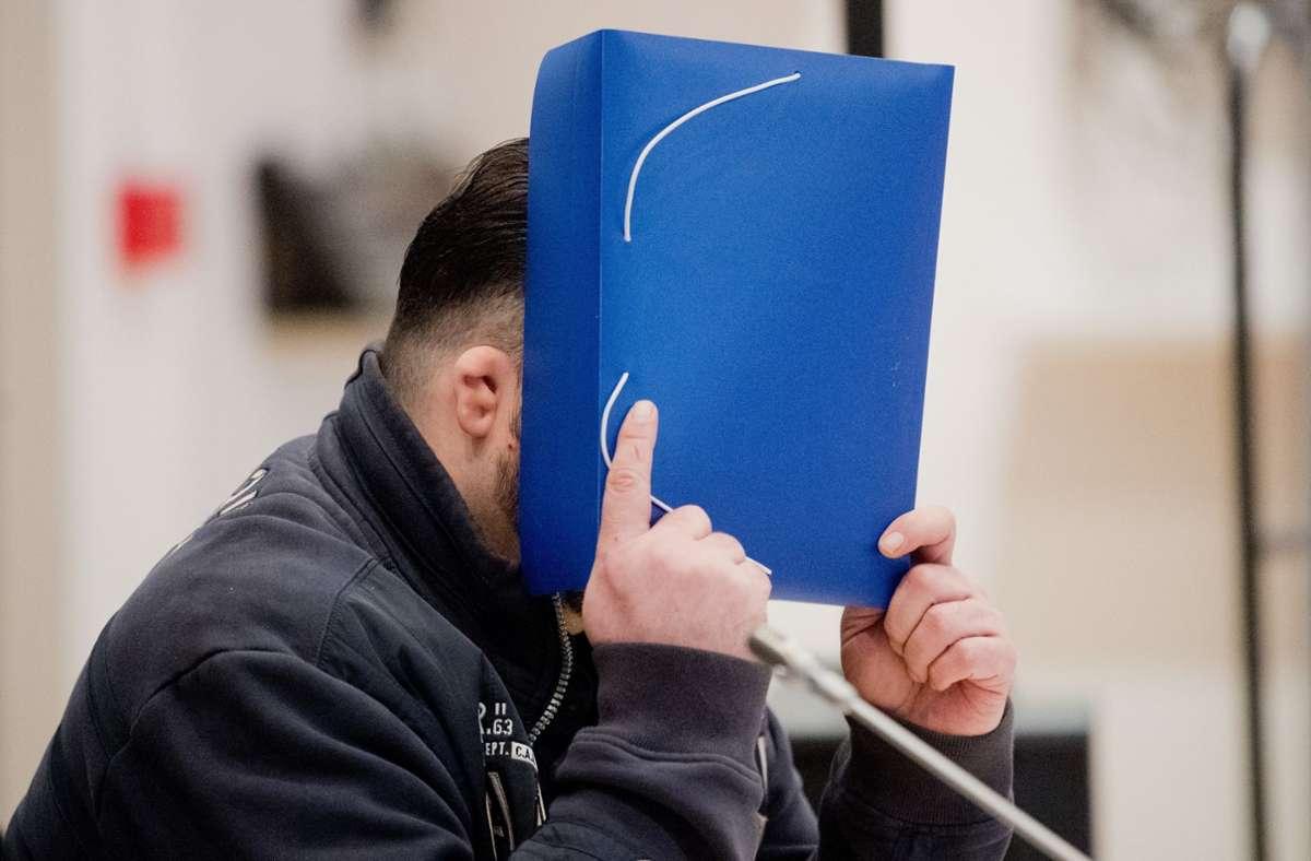 Niels Högel, wie er sein Gesicht während der Verhandlung verbarg. (Archivbild) Foto: dpa/Julian Stratenschulte