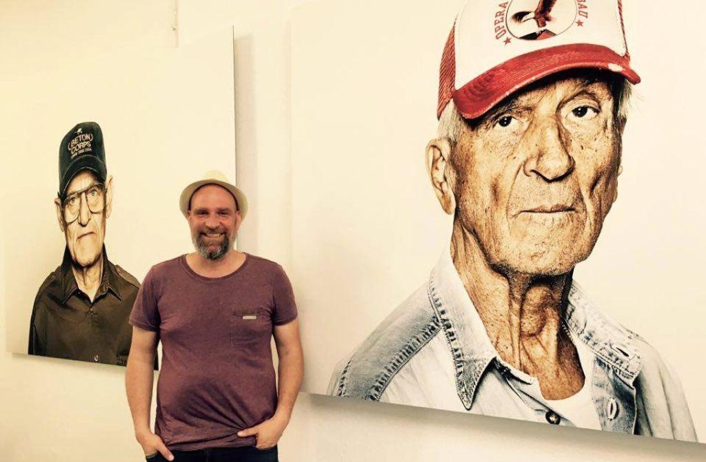 Darius Ramazani vor seinen Bildern der Ausstellung Veterans im Christian Weisser Design Studio. Foto: Tanja Simoncev