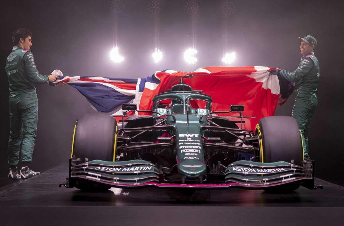 Sebastian Vettel (re.) und Teamkollege Lance Stroll ziehen die riesigen Union Jack vom neuen Formel-1-Boliden Aston Martin AM R21 Foto: dpa/Aston Martin