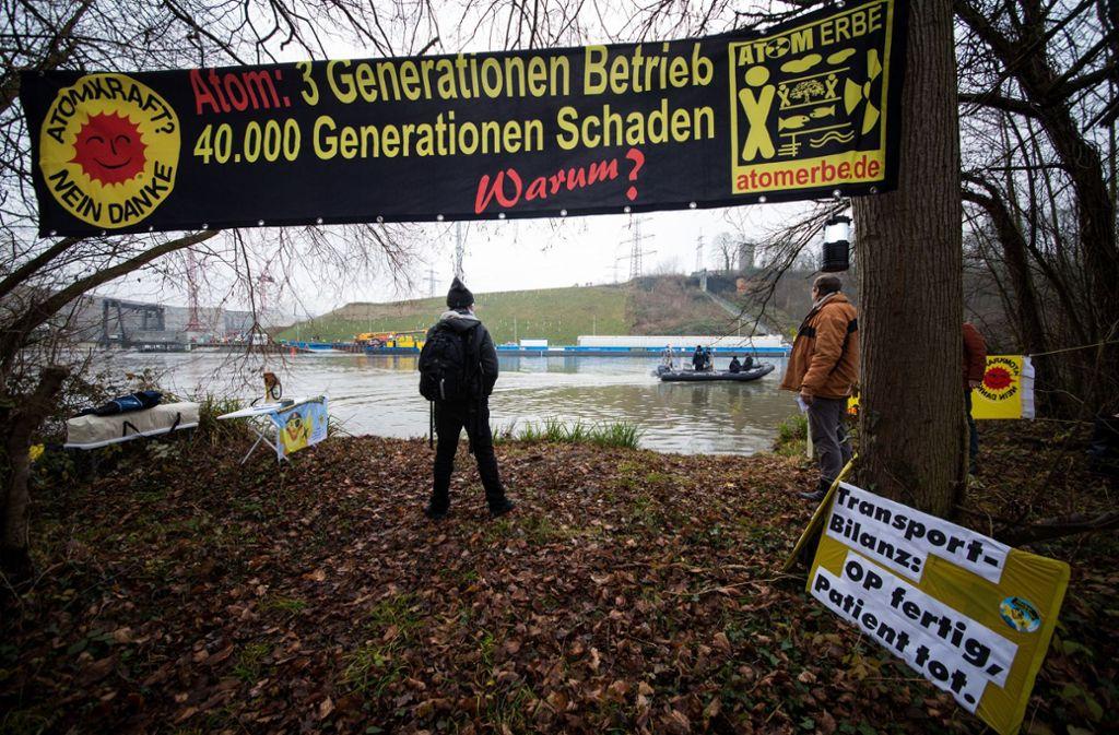 Atomkraftgegner beobachten, wie auf der anderen Seite des Neckars der Castortransport aus Obrigheim am Kernkraftwerk in Neckarwestheim vor Anker geht. Foto: dpa