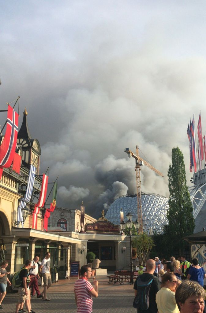 Zahlreiche Besucher des Europa-Parks verfolgen das Feuer aus der Ferne. Foto: dpa