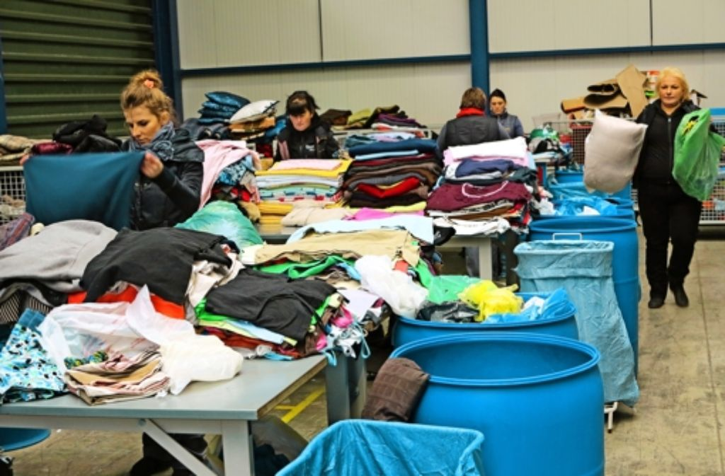 Am Sortiertisch sehen sich die Frauen die Kleidungsstücke genau an. Foto: Birgit Klein