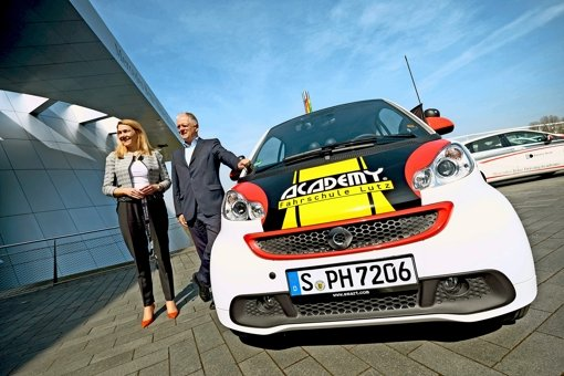 Eva Wiese, die Leiterin des Produktmanagements E-Mobility bei  Daimler, zeigt OB Fritz Kuhn einen der elektrisch angetriebenen Fahrschul-Flitzer. Foto: Lichtgut/Heinz Heiss